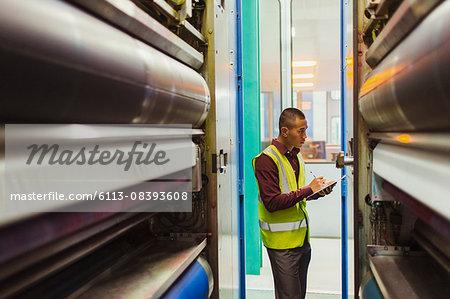 Engineer with clipboard examining printing press machinery