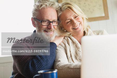 Smiling senior couple using laptop in kitchen
