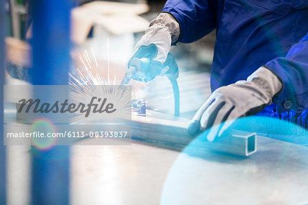 Welder welding steel in factory