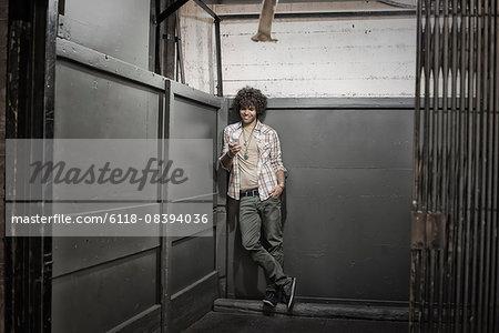 Loft living. A man in a loft elevator checking his phone.