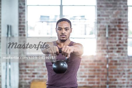 Muscular man lifting kettle bells