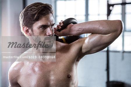 Fit shirtless man lifting kettlebell