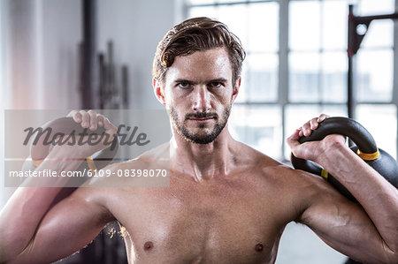 Fit shirtless man lifting kettlebells
