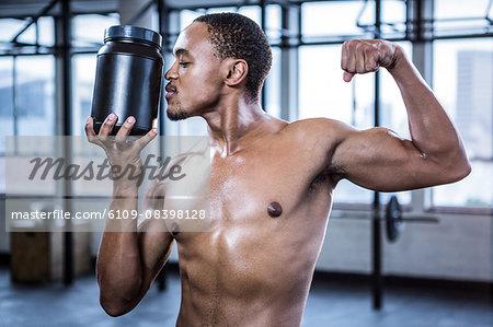 Fit shirtless man kissing protein powder