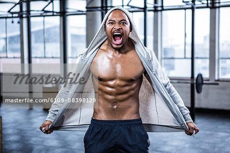 Fit shirtless man shouting at camera