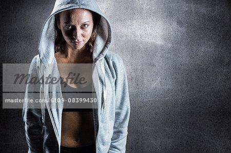 Composite image of portrait of female athlete in hood