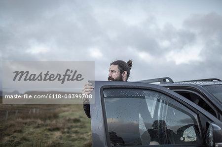A man standing by an open car door, looking around him, under a cloudy wintery sky.