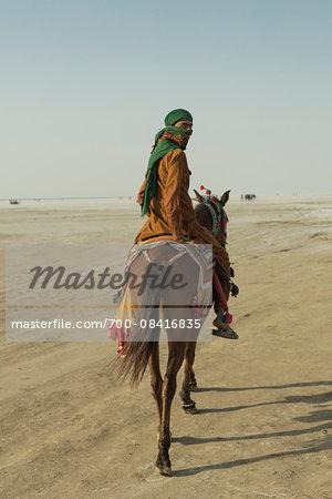 Nomad tribesman on horse back riding on the salt desert, Dordo, Kutch, Gujarat, India.