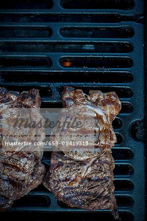 Grilled rib-eye steaks on a barbecue