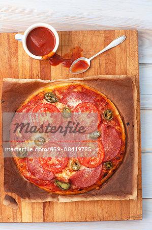 A pizza with salami and jalapeños