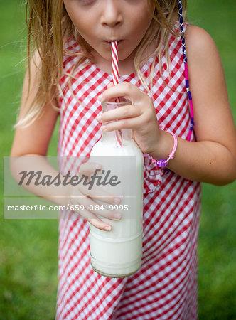 A little girl drinking a bottle of vegan milk in a garden