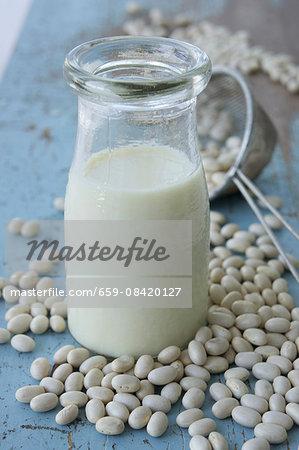 A bottle of soya milk and soya beans