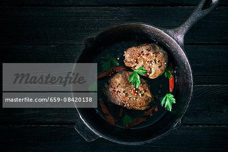 Pepper steaks in a black cast-iron pan