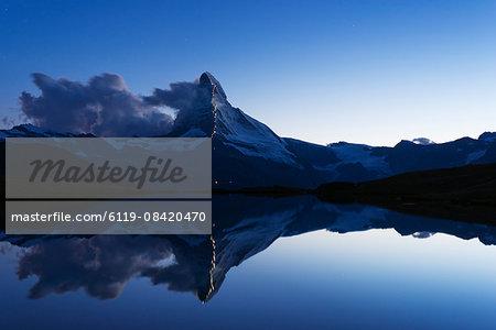 The Matterhorn, 4478m, illuminated in honour of the 150th anniversary of the first ascent, Stellisee lake, Zermatt, Valais, Swiss Alps, Switzerland, Europe