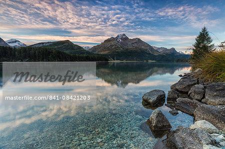 Pink sky at dawn illuminates the peaks reflected in Lake Sils, Engadine, Canton of Graubunden, Switzerland, Europe