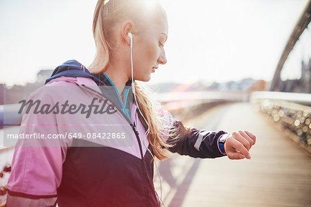 Mid adult female runner checking time on footbridge