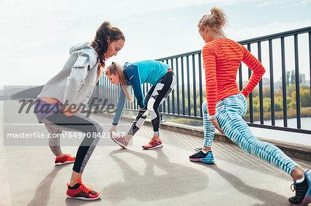 Three female runners doing warm up exercise on footbridge