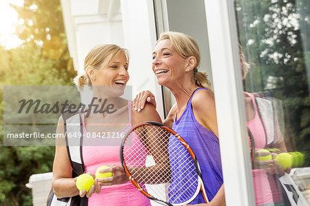 Two mature women preparing to play tennis at patio door