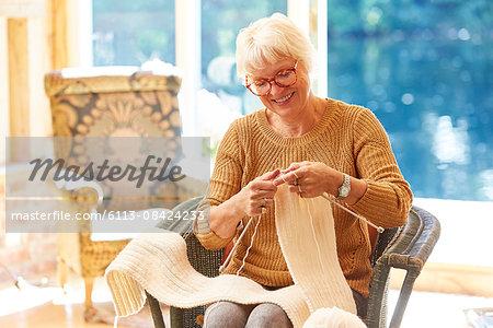 Senior woman knitting in living room