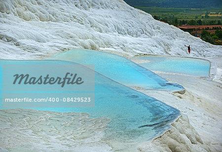 Nature wonder Pamukkale - Turkey landmark. White travertines are surrounded azure lakes.