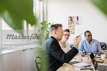 Mature businessman explaining multi ethnic colleague during meeting