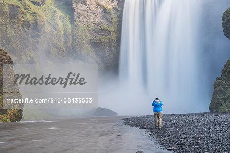 Tourist taking a photo of Skogafoss Waterfall, Skogar, South Region (Sudurland), Iceland, Polar Regions