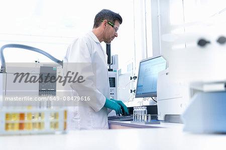 Male scientist at workstation testing oil samples