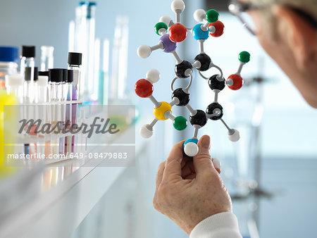 Scientist holding molecular model in laboratory