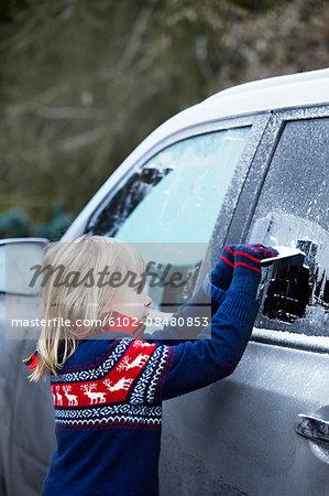 Girl scraping ice from car window