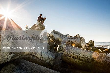 Young man holding skateboard, sitting on breakwater, looking towards ocean
