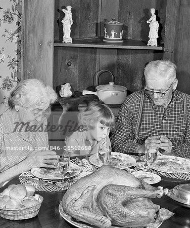 1950s FAMILY THANKSGIVING DINNER PRAYING GIRL AND GRANDPARENTS