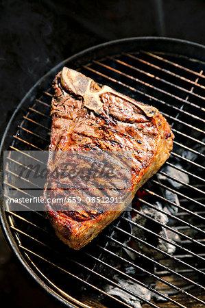 A T-bone steak on a barbecue