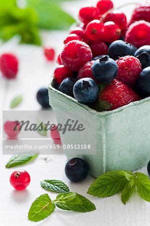 Fresh berries berries and fresh mint leaves in a cardboard punnet
