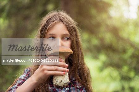 Girl smelling mushroom
