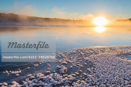 Sun over lake in winter scenery