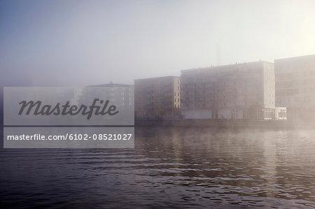 Buildings at water in fog