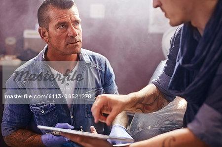 Man with digital tablet talking to tattoo artist