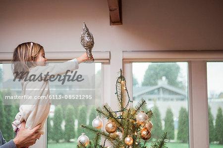 Toddler girl putting star on Christmas tree