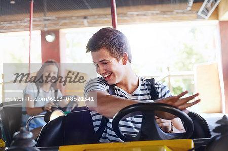 Smiling young man riding bumper cars at amusement park