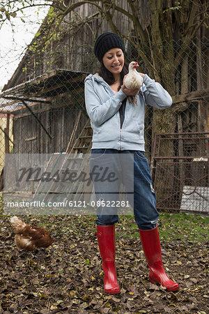 Farmer woman with white chicken bird in farm, Bavaria, Germany