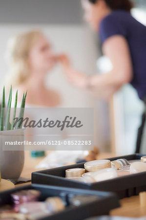 Bridesmaid applying makeup on bride, Fürstenfeldbruck, Bavaria, Germany