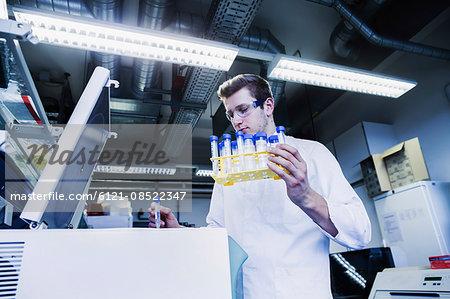 Young male scientist examining test tube in a pharmacy laboratory, Freiburg Im Breisgau, Baden-Württemberg, Germany