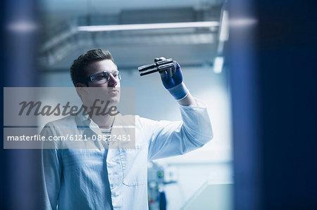 Young male scientist working in an optical laboratory, Freiburg Im Breisgau, Baden-Württemberg, Germany