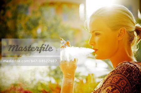 Landscape image of a woman smoking a cigarette