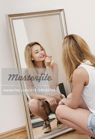 Girl putting on lipstick