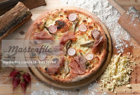 Overhead view of parma ham and radish pizza