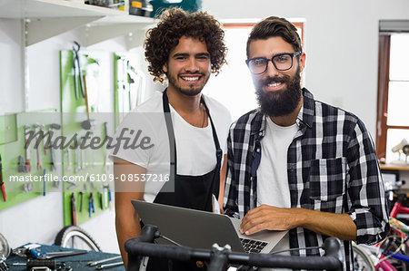 Bike mechanic checking colleague laptop