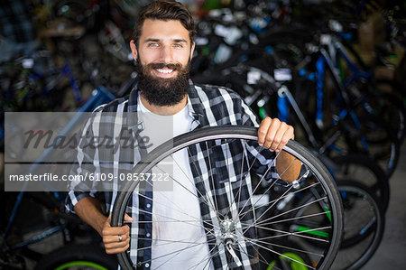 Bike mechanic holding a bicycle wheel