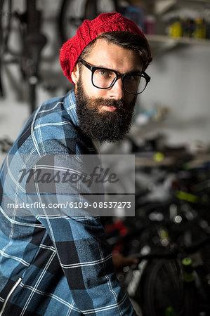 Hipster bike mechanic standing