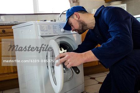 Handyman repairing a washing machine